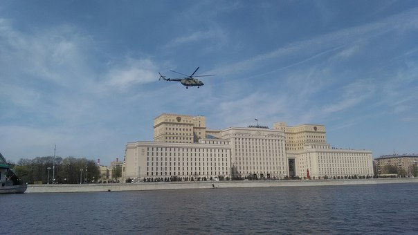 На фоне Минобра летит вертолёт прямо над рекой