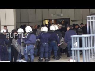 Греция: Протестующие бросают камни и сигнальные ракеты в качестве членов Золотой Зари перед судом.