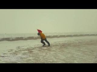 Метеоролог борется с ветром за установку флага