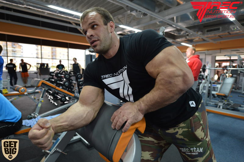 Denis Cyplenkov flexing forearm at Scott Bench │ Photo Source: Trec Nutrition