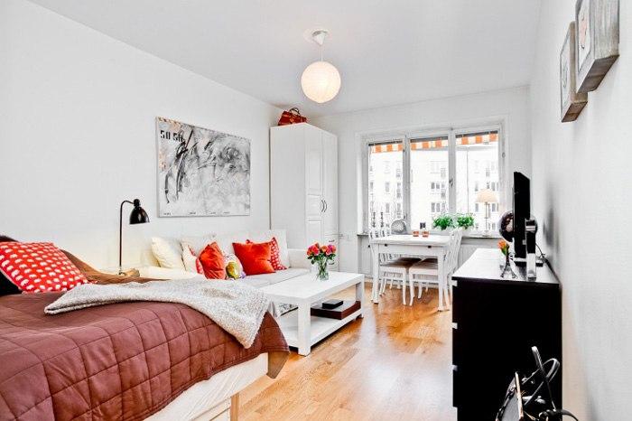 Интерьер квартиры-студии 28 м в Европе с угловой кухней в холле и яркими деталями.