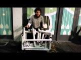 Уличный музыкант играет на водопроводных трубах