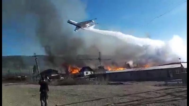 Самолет Бе-200ЧС сливает воду на горящие пиломатериалы на заводе в Кежемском районе