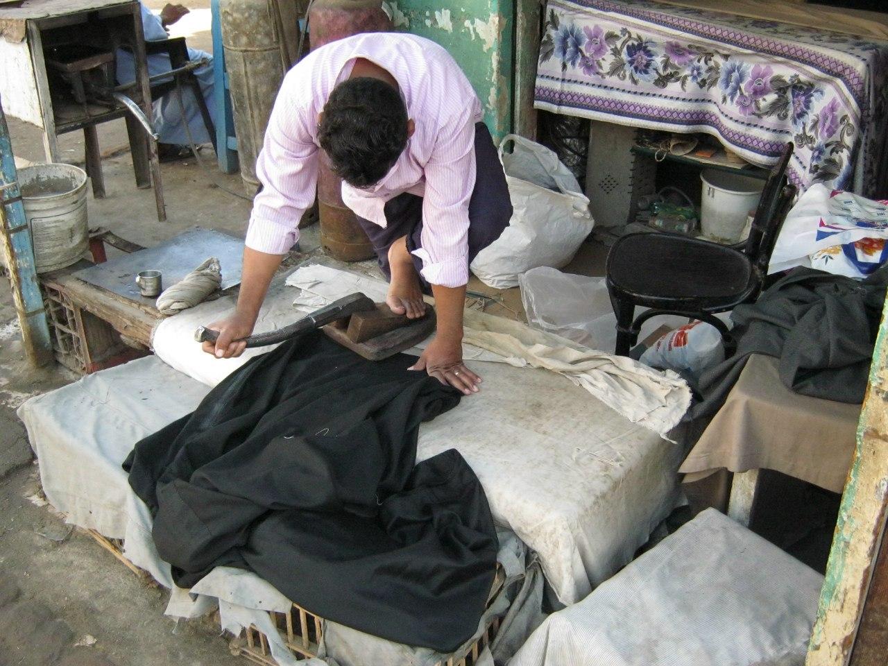 традиционный горячий утюг гладит одежду (на базаре в Асуане)