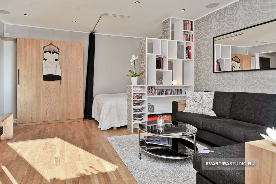 Зонирование гостиной-спальни разноуровневым (ступенчатым) стеллажом.