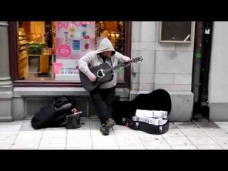 Уличный музыкант играет и поет около магазина на гитаре
