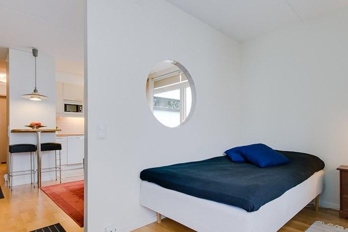 Квартира 34 м с оригинальной перегородкой с круглым окном для отделения спальной зоны.