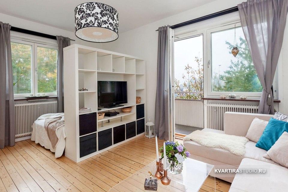 Разделение комнаты на гостиную и спальню высоким белым стеллажом.