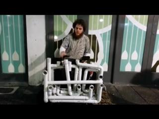 Уличный музыкант играет на водопроводных трубах Музыка Труба