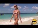 стройная девушка в глубоком микро бикини загорает на пляже