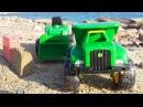Видео на пляже. Грейдер и самосвал строят замок из песка. Toys and vehicles on the beach
