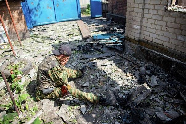 Ополченец из поселка Семеновка под Славянском во дворе своего дома, разрушенного в результате попадания снаряда во время ночного обстрела украинскими военными