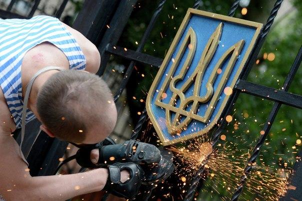 Боец ополчения Луганской народной республики срезает герб Украины с ворот здания областной администрации в Луганске