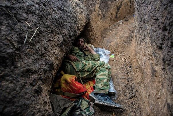 Ополченец отдыхает на передовой позиции в поселке Семеновка