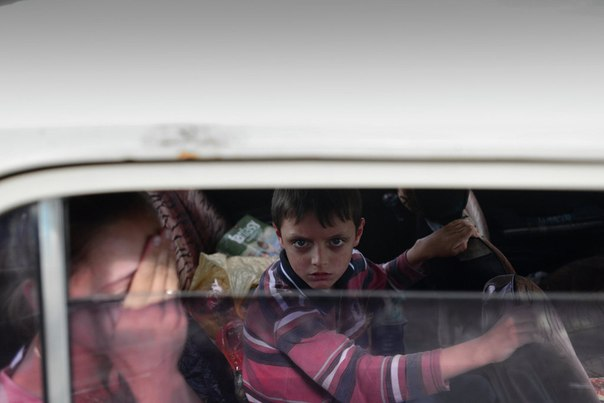 Беженцы на окраине Луганска после артиллерийского обстрела поселка Металлист
