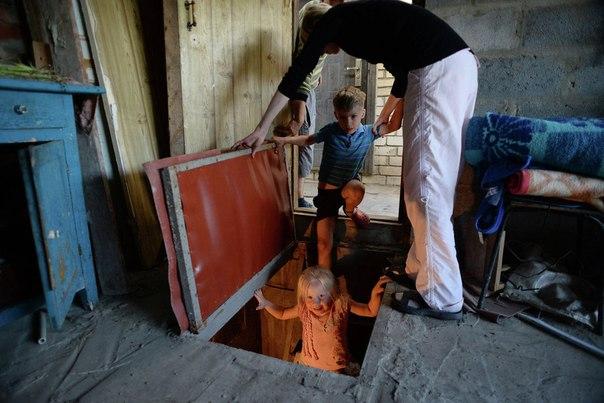 Семья у входа в подвал, оборудованный под бомбоубежище, в Краматорске Донецкой области