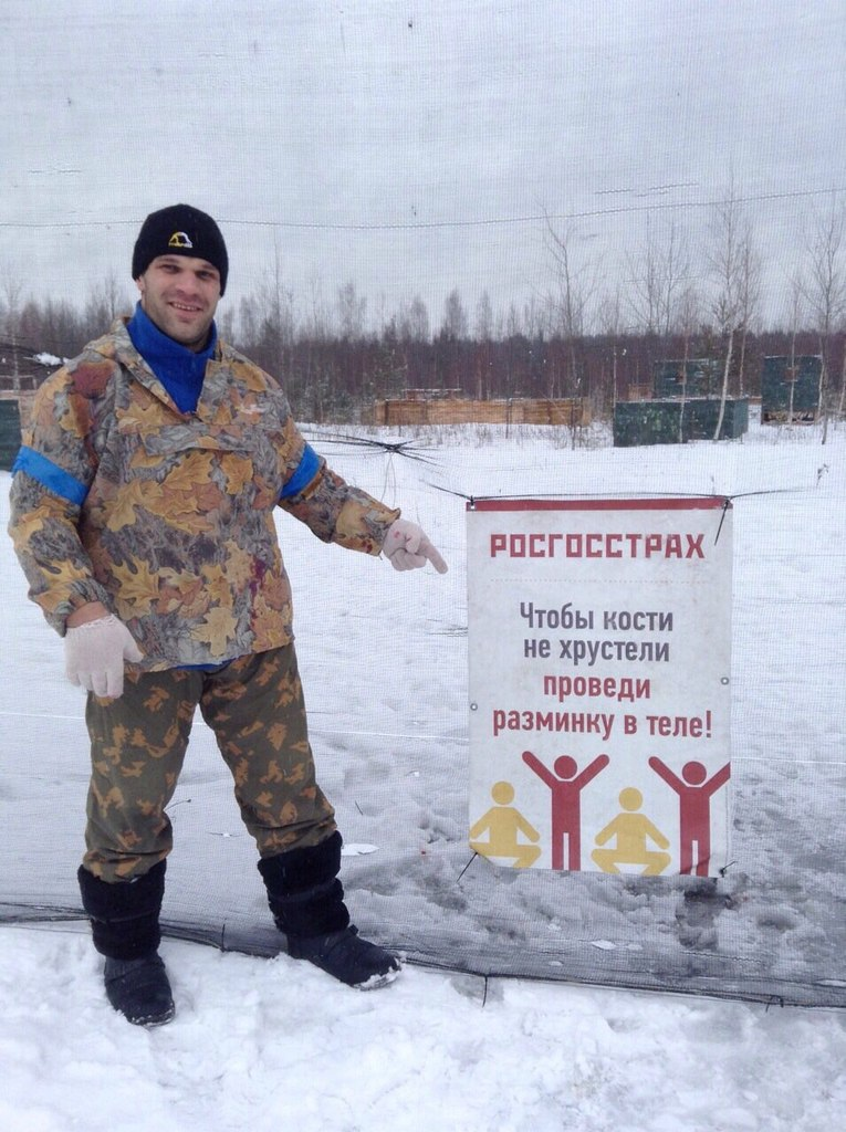 Denis Cyplenkov in military camouflage clothes points to a physical exercise banner │ Image Source: Denis Tsyplenkov