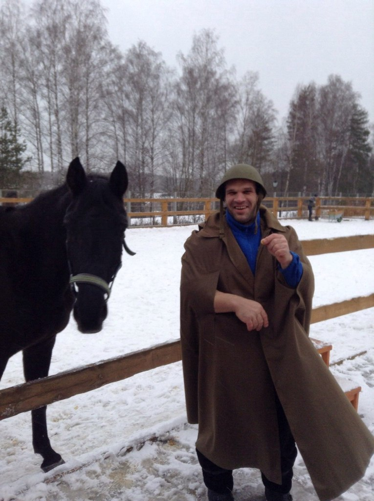 Denis Cyplenkov in military clothes laughs next to a horse  │ Image Source: Denis Tsyplenkov