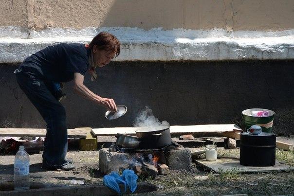 Жительница Шахтерска готовит еду на костре рядом с убежищем в подвале жилого дома