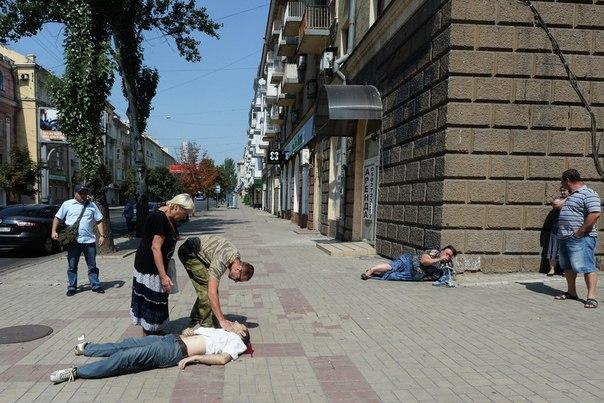 Жители Донецка на одной из улиц города, где произошел обстрел мирных жителей