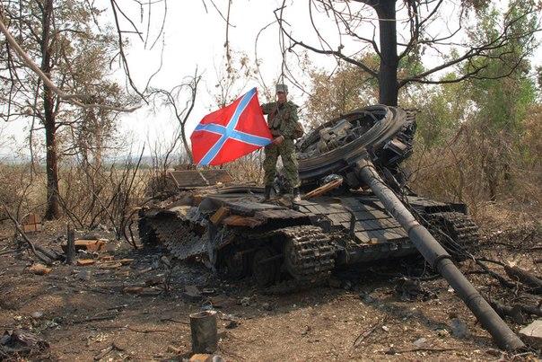 Ополченец Донецкой народной республики с флагом Новороссии на уничтоженном танке украинских силовиков