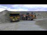 Гигантский колесный погрузчик Caterpillar 994 работает в связке с самосвалом
