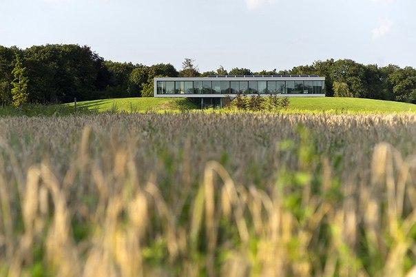 Дом в живописной деревне Нидерландов Частный дом Bridge спроектирован студией 123DV и построен в деревне Зелем, Нидерланды. Его нижний уровень практически полностью утопает между двумя небольшими травянистыми холмами, искусственно созданными специально для данного проекта. В этой части резиденции расположены прихожая и гараж. Второй этаж дома является жилым и представлен гостиной, кухней, столовой, спальнями и ванными комнатами. Панорамные окна практически по всему периметру здания не только…