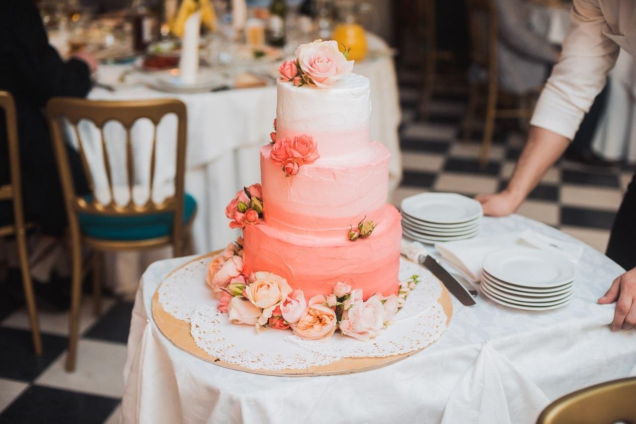 свадебный торт в коралловых оттенках, украшенный цветами