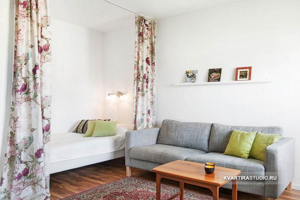 Зонирование комнаты на гостиную и спальню шторами с размещением кровати в нише.