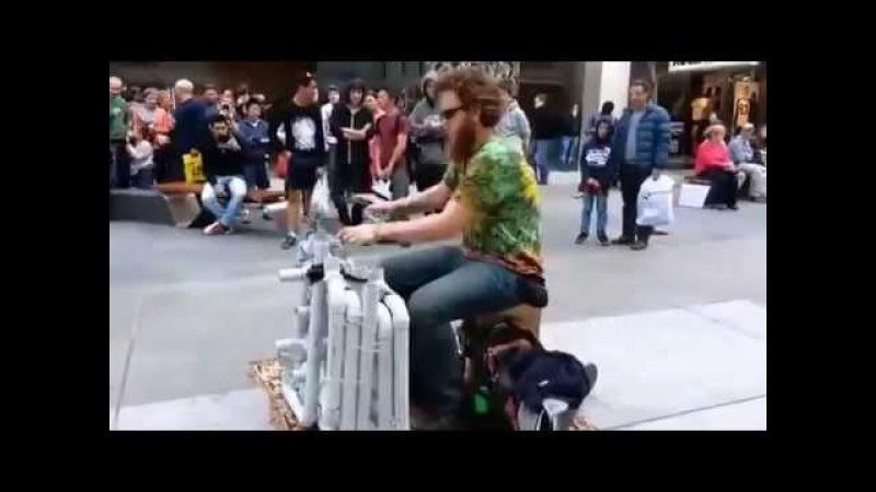 Уличный музыкант играет наневероятном самодельном инструменте