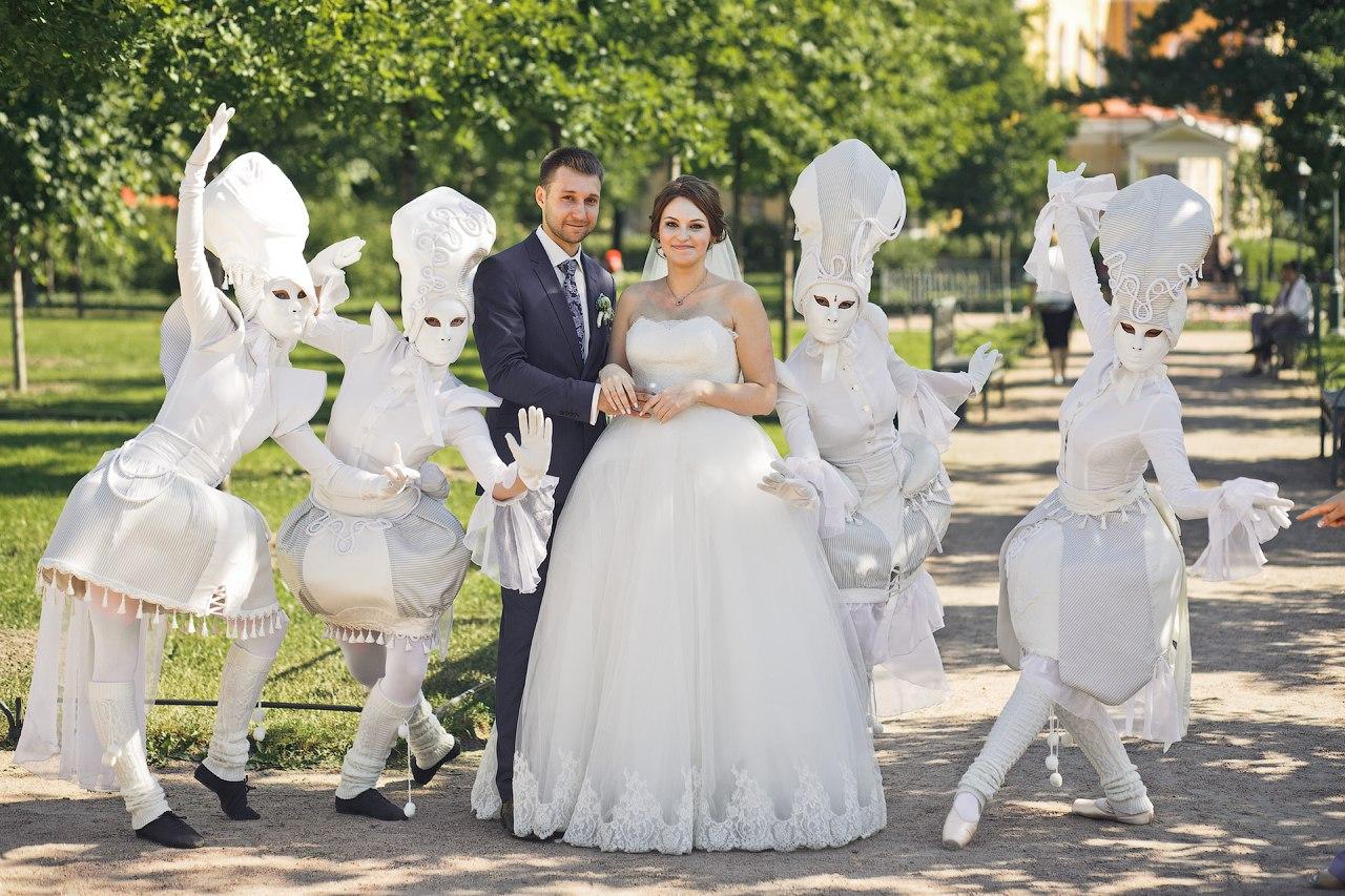 жених с невестой в окружении уличного театра