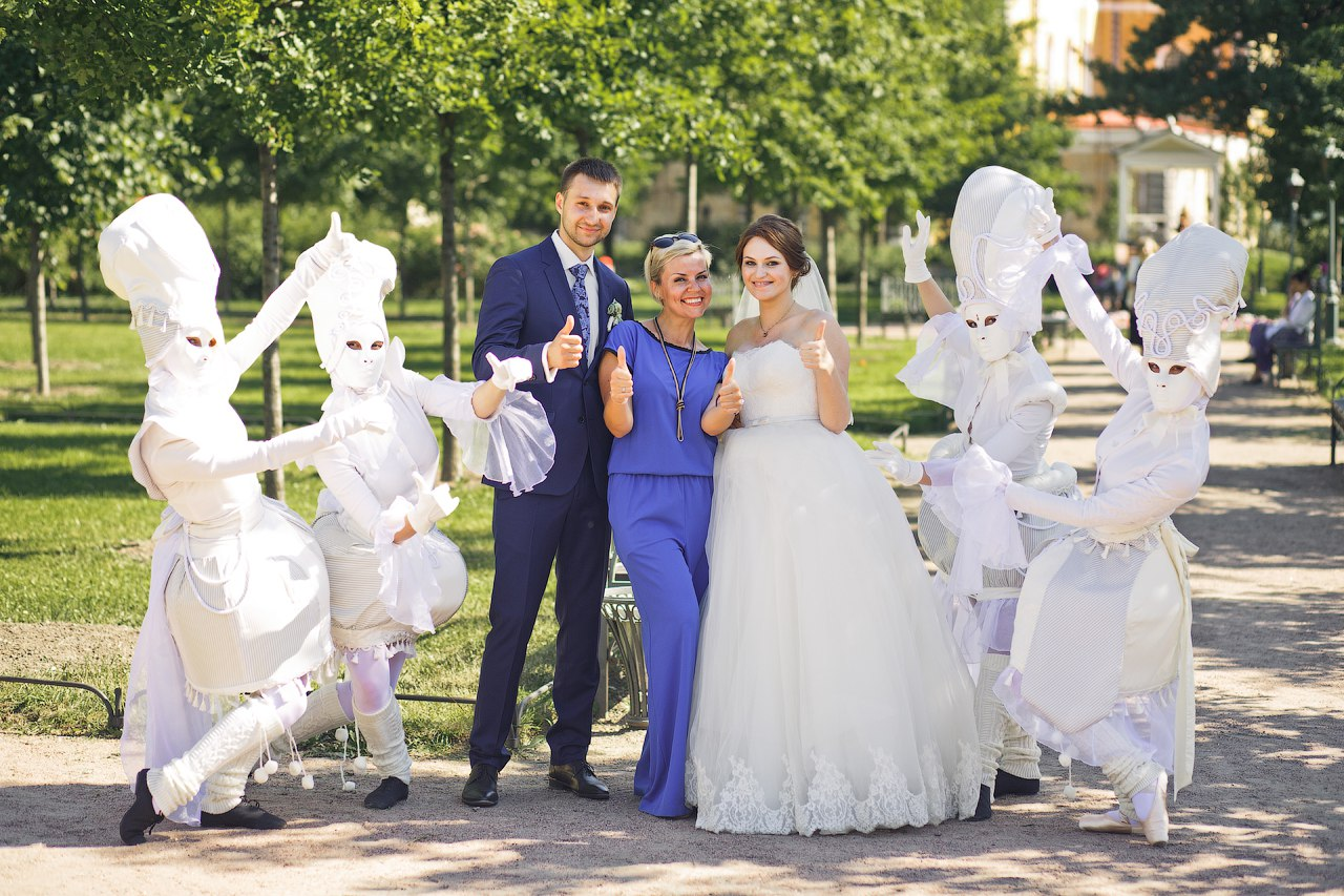 организатор с женихом и невестой в окружении актеров уличного театра