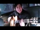 Парень красиво играет на гитаре и поет песню Четыре татарина и блатной казах
