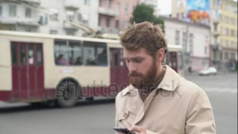 Stock-footage-handheld-shot-with-tilt-up-of-stylish-young-man-with-beard-in-trench-coat-walking-along-street-and-l