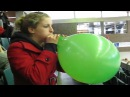 Cool girl blowing up a big green balloon until it pops