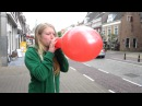 Girl blowing up a tight red balloon until it pops outside