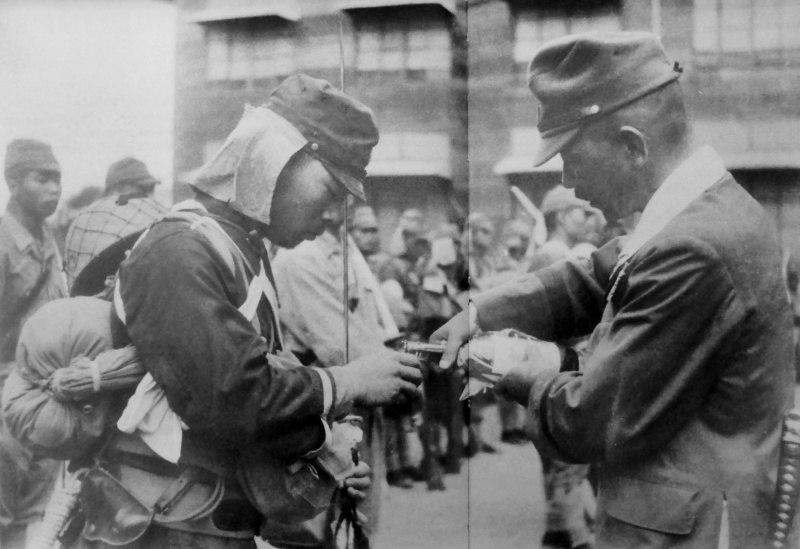 """Командующий японской 4-ой воздушной армии генерал-лейтенант Киодзи Томинага наливает саке лейтенанту Шигео Нака перед строем солдат """"Каору"""" (воздушно-десантное штурмовое подразделение) в Маниле до переброски подразделения на операцию на острове Лейте."""