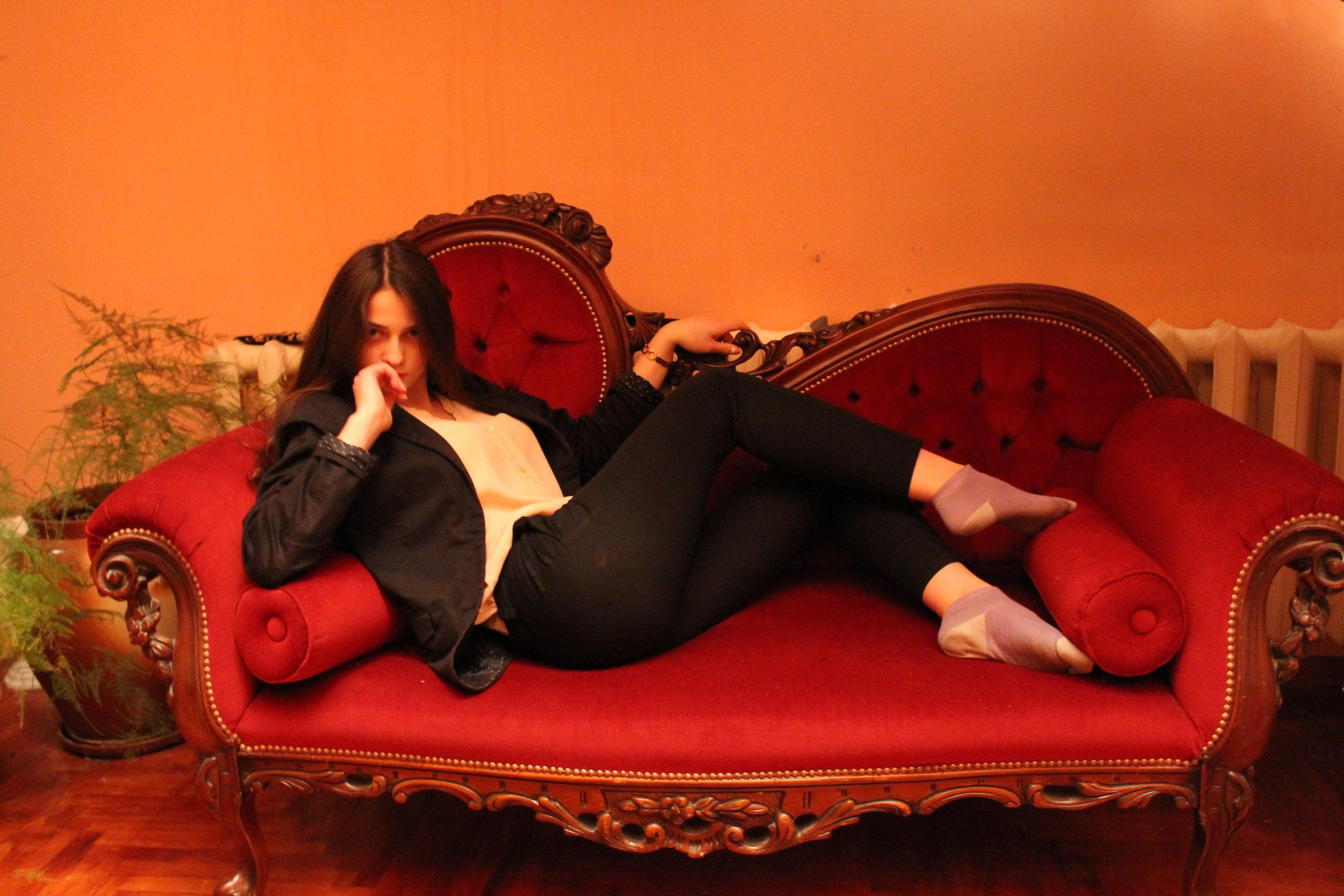 Стройная шатенка на красном диване