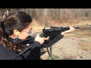 Girls shoots her first automatic weapon.