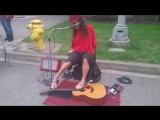 Безрукий уличный музыкант играет на гитаре.