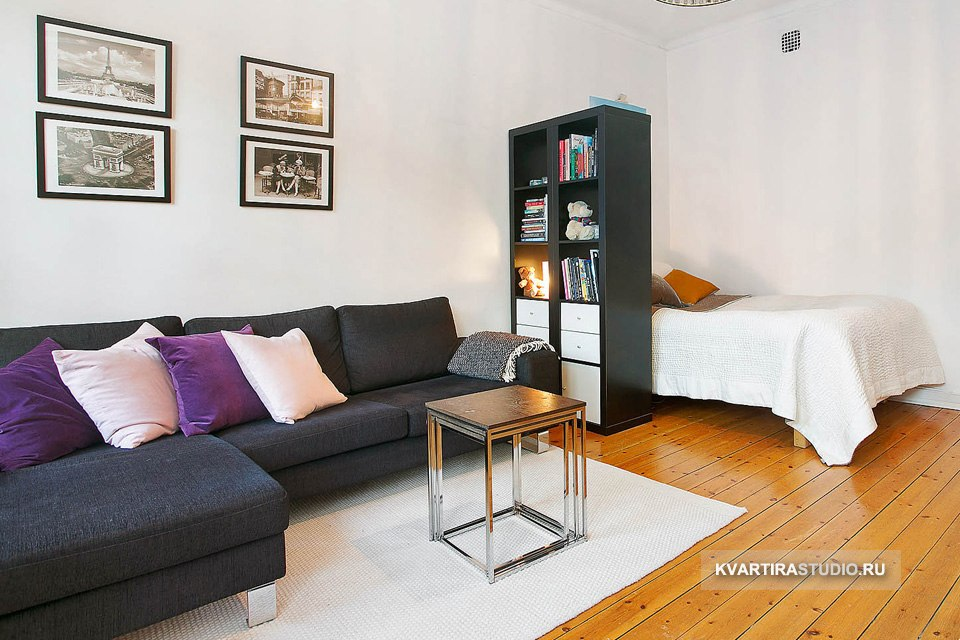 Зонирование комнаты на гостиную и спальню высоким черным стеллажом – http://kvartirastudio.