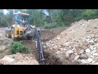 Экскаватор трактор копает задним ковшом траншеи котлован Канаш