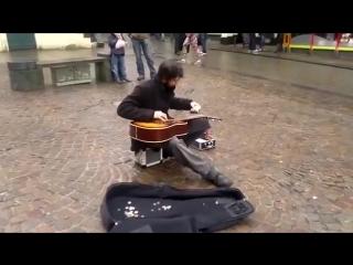 Уличный гитарист играет как профессионал.
