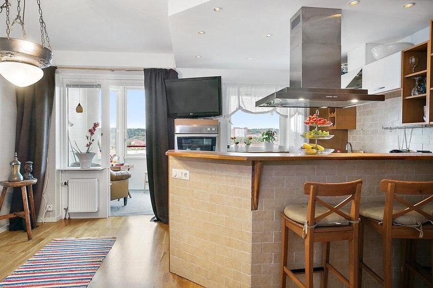 Интерьер квартиры-студии 25 м с изогнутой барной стойкой и откидной кроватью.