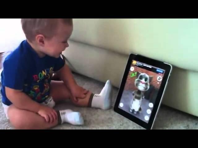 Baby talks with cat on iPad