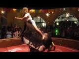 Девушка верхом на механическом быке .