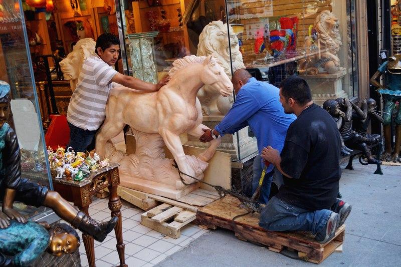Люди волокут статую