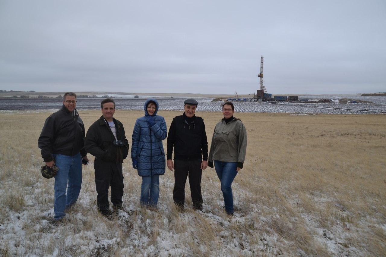 Участники нефтяного тура у одиночной нефтяной вышки в степи Общего Сырта