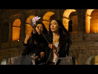 Funny young Korean asian girls take selfie pictures near Colosseum in Rome Italy
