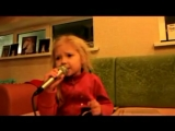 Маленькая девочка поёт песню, рюмка водки на столе
